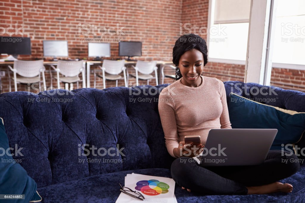 Businesswoman Working On Sofa In Modern Creative Office stock photo