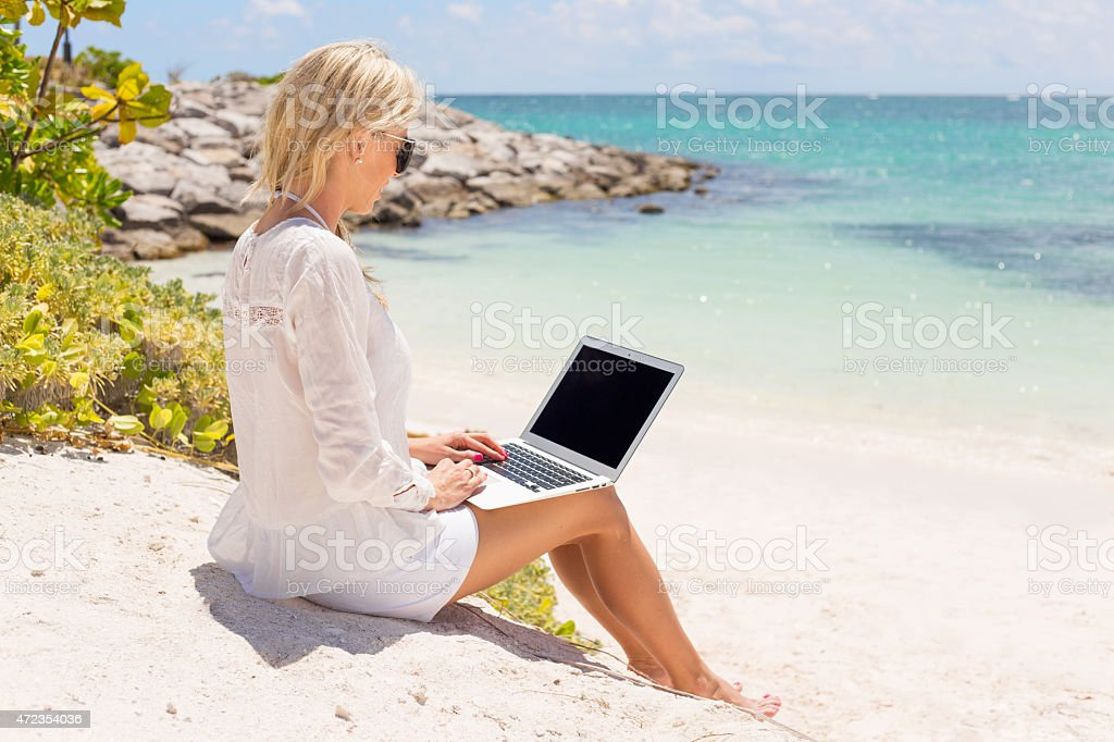 Businesswoman working with computer on the beach stock photo