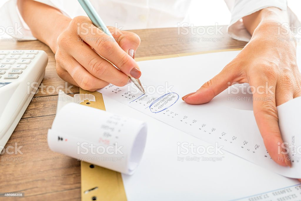 Businesswoman Works with Receipts at her Desk stock photo