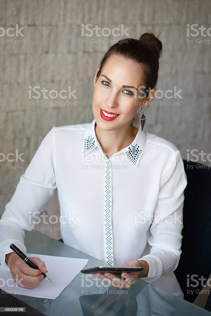 Businesswoman write on blank paper and holding tablet stock photo