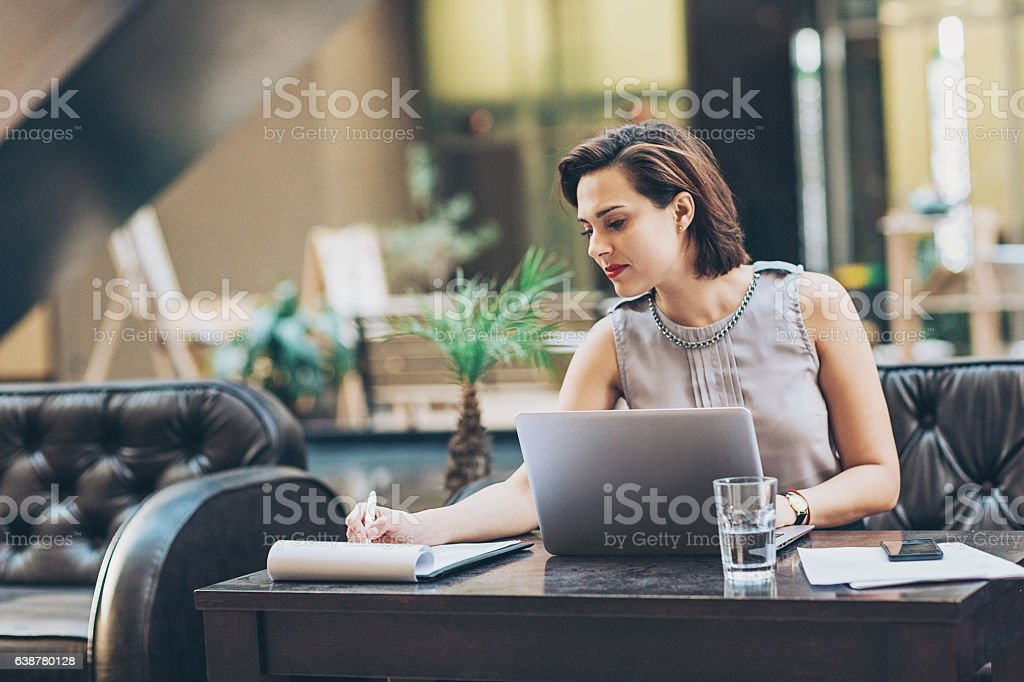 Businesswoman writing documents stock photo