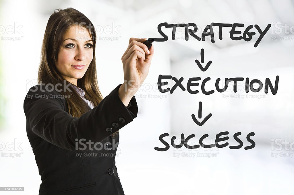 Businesswoman writing down key elements leading to success stock photo