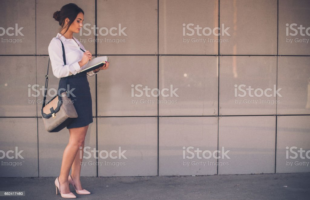 Businesswoman writing her busy schedule in the note book stock photo