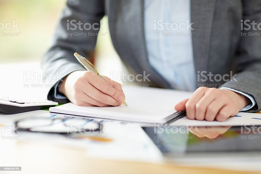 Businesswoman writing in note pad while calculating finance stock photo