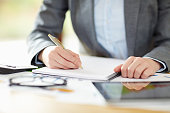Businesswoman writing in note pad while calculating finance