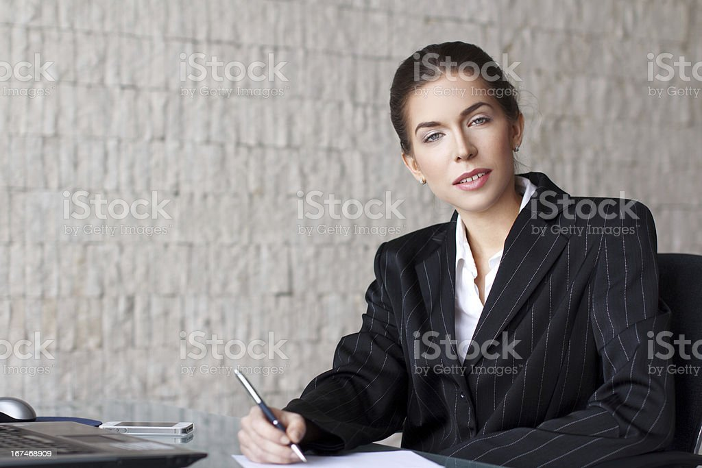 Businesswoman writing letter at desk royalty-free stock photo