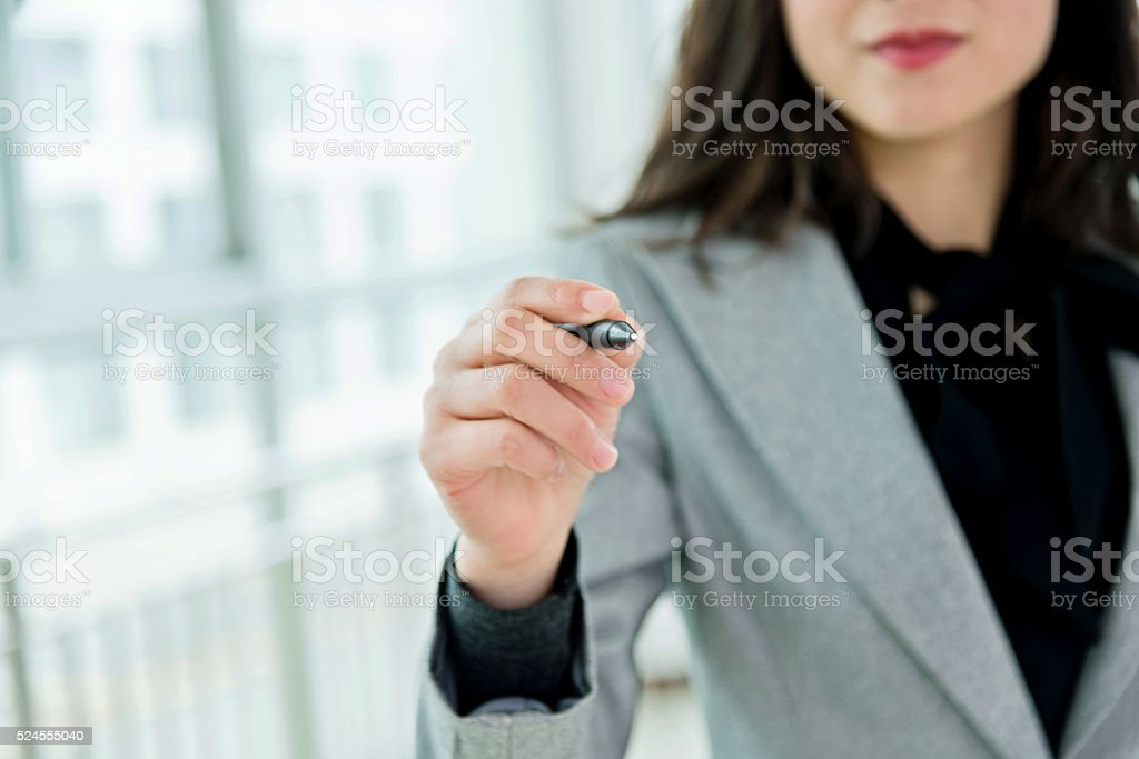 Businesswoman writing on empty space stock photo
