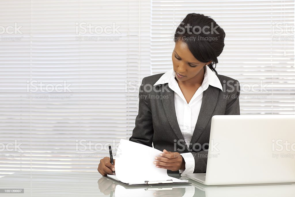 Businesswoman writing report at office royalty-free stock photo