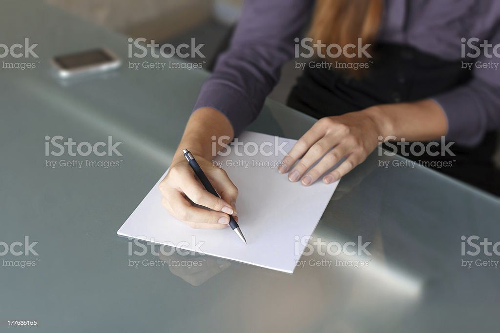 Businesswoman writing with pen on paper royalty-free stock photo