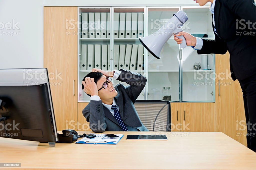 Businesswoman yelling at colleague through a bullhorn stock photo