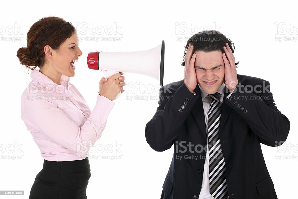 Businesswoman yelling through megaphone at businessman stock photo