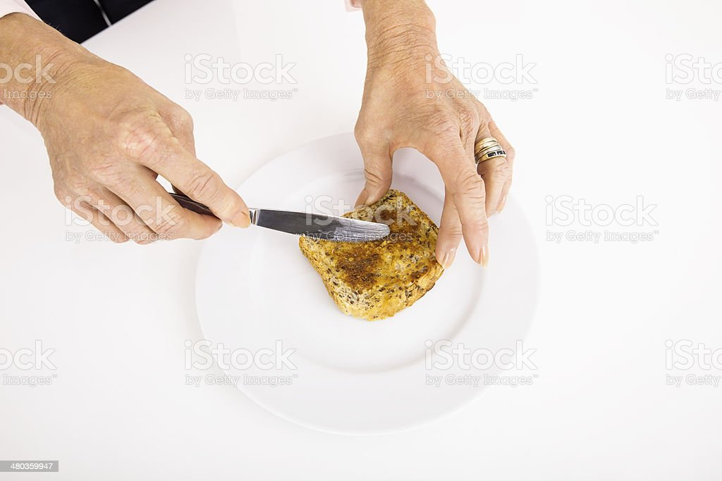 Businesswoman's hands spreading butter on bread stock photo