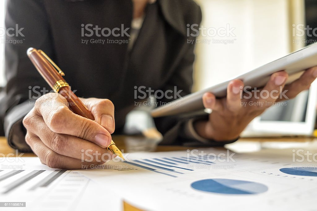 Businesswomen analyzing investment charts in meeting room, Accou stock photo