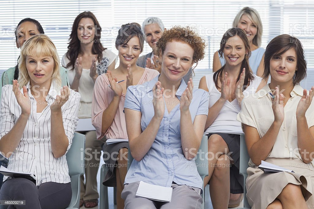 Businesswomen applauding colleague after presentation stock photo