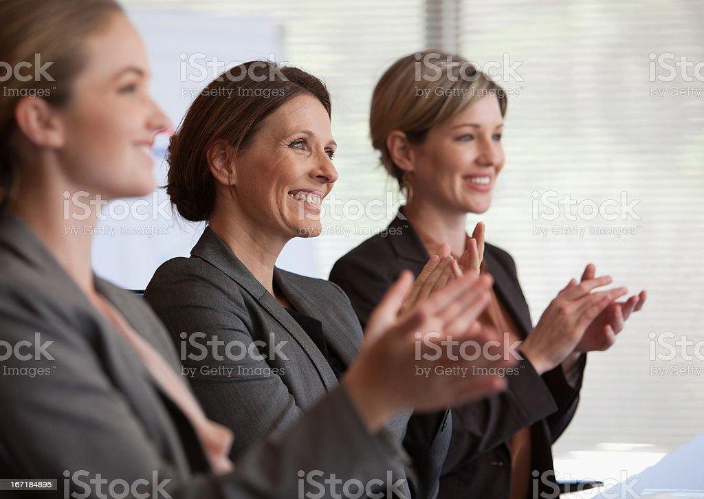 Businesswomen clapping in conference room stock photo