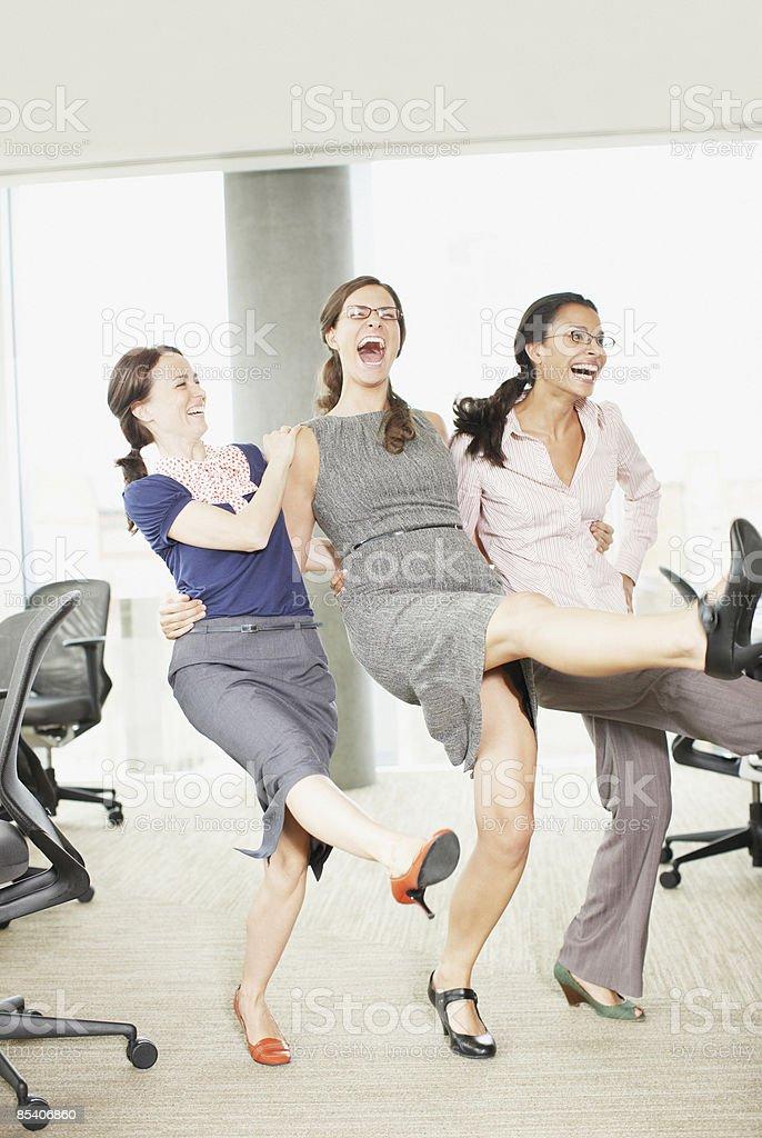 Businesswomen dancing in office royalty-free stock photo