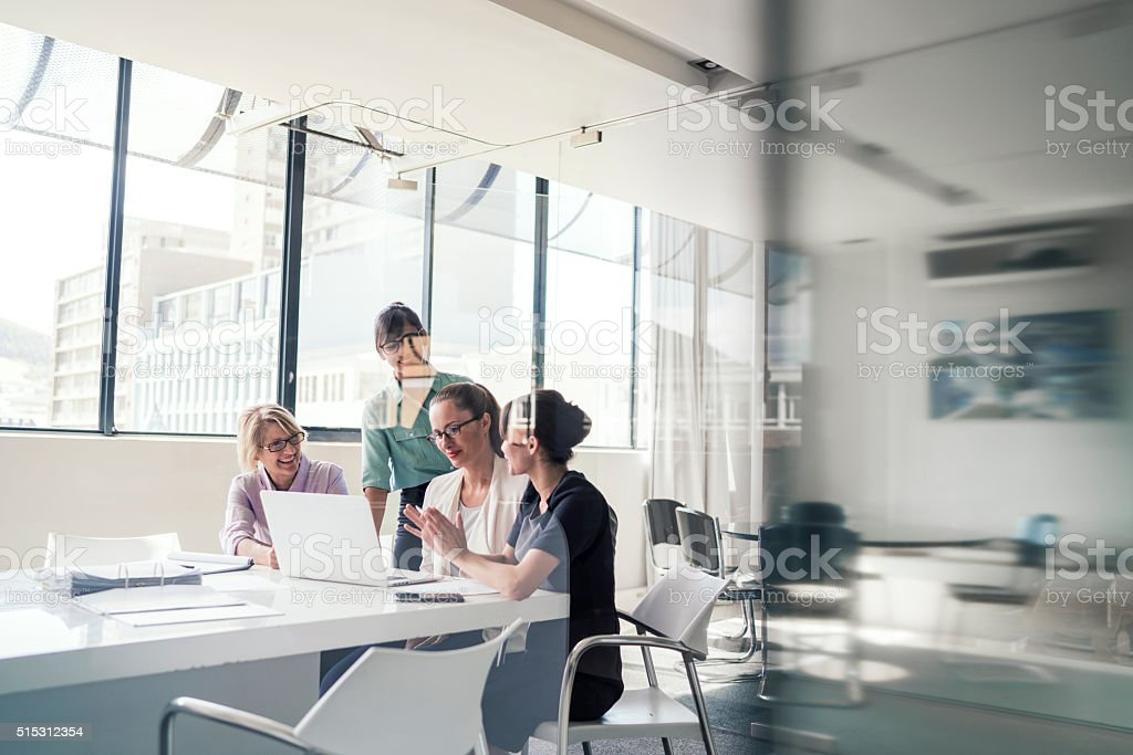 Businesswomen discussing over laptop in office stock photo