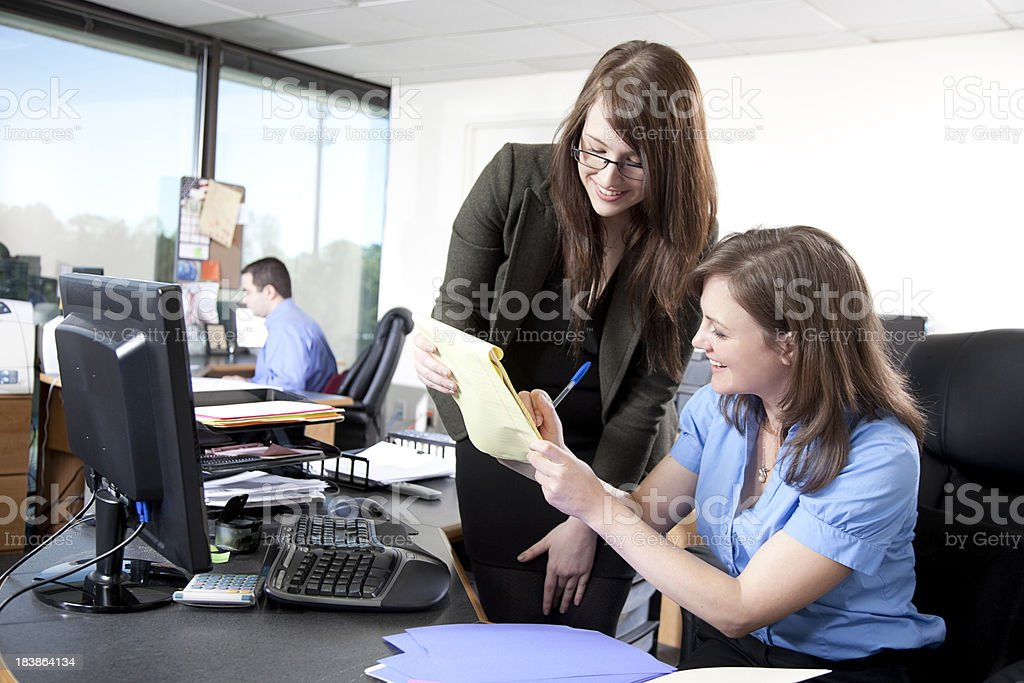 Businesswomen discussing paperwork royalty-free stock photo