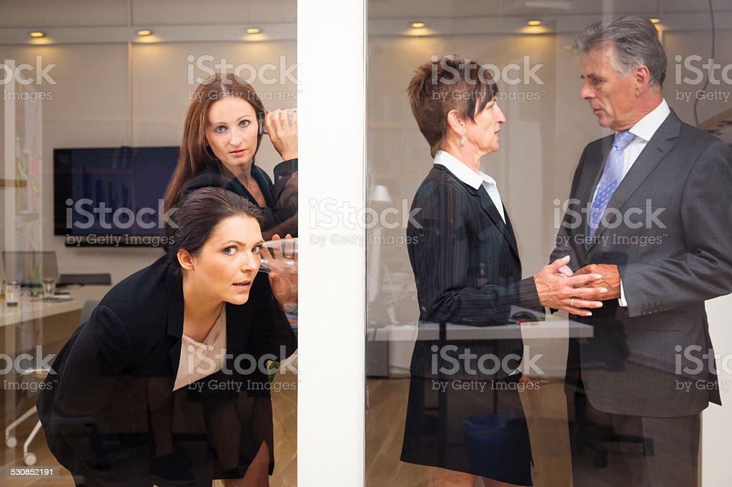businesswomen eavesdropping on their superiors stock photo