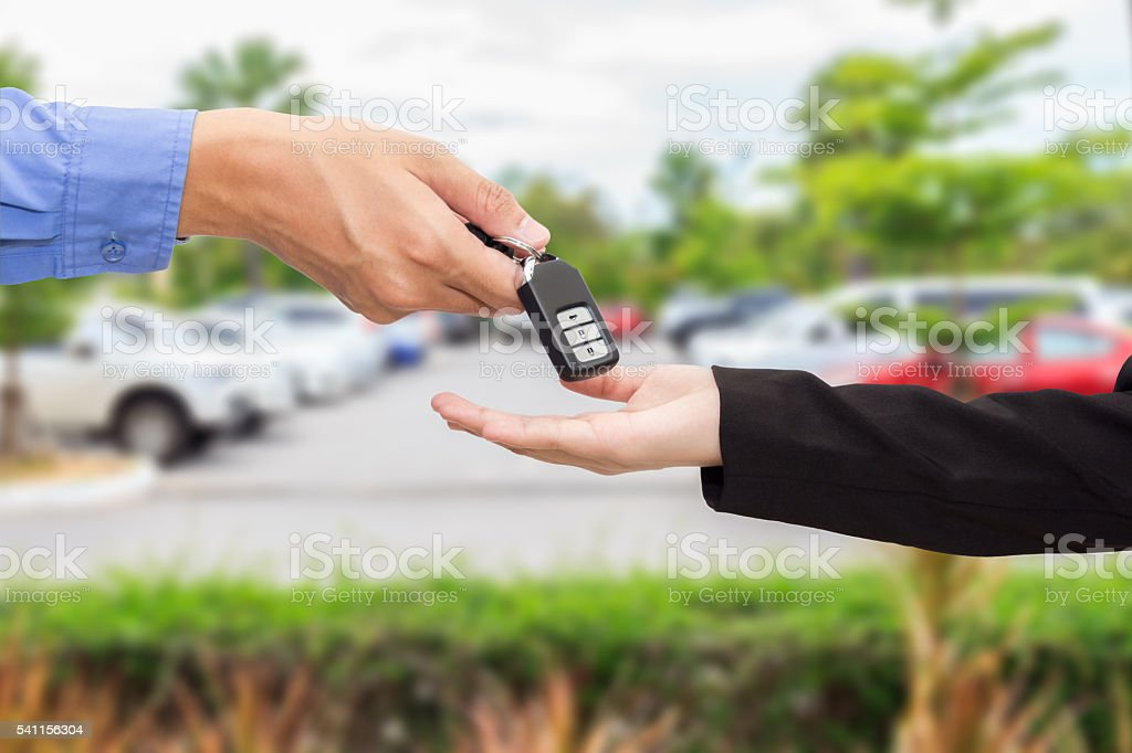 Businesswomen giving a key car to businessman at car parking stock photo