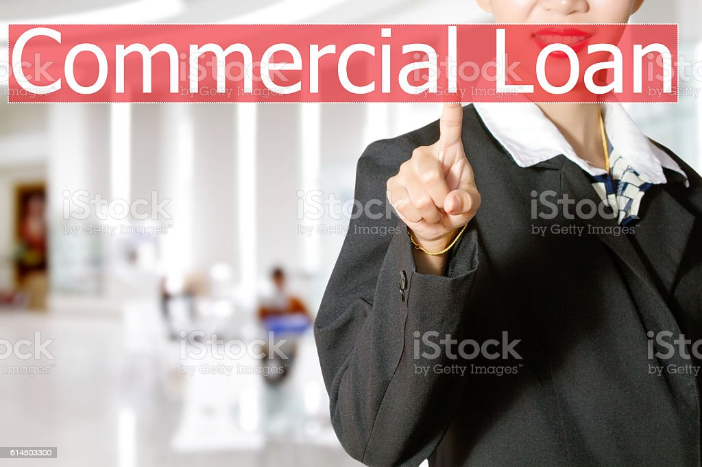 Businesswomen hand touching COMMERCIAL LOAN sign on virtual stock photo