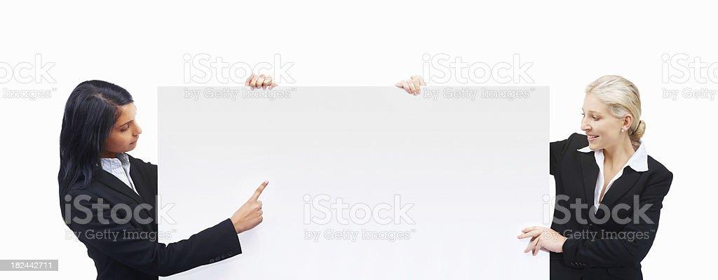 Businesswomen holding an empty billboard royalty-free stock photo
