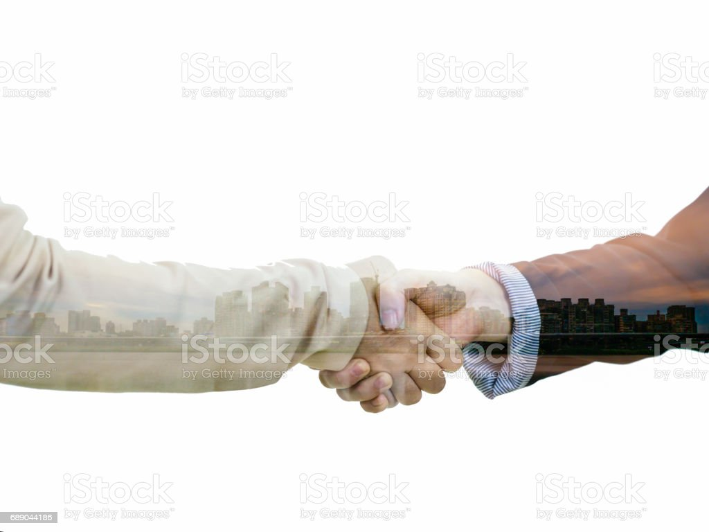 Businesswomen in casual attire shaking hands with cityscape double exposure stock photo