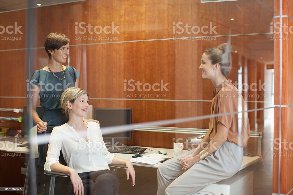 Businesswomen laughing in office stock photo