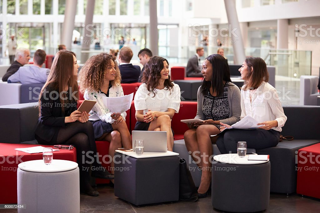 Businesswomen Meeting In Busy Lobby Of Modern Office stock photo