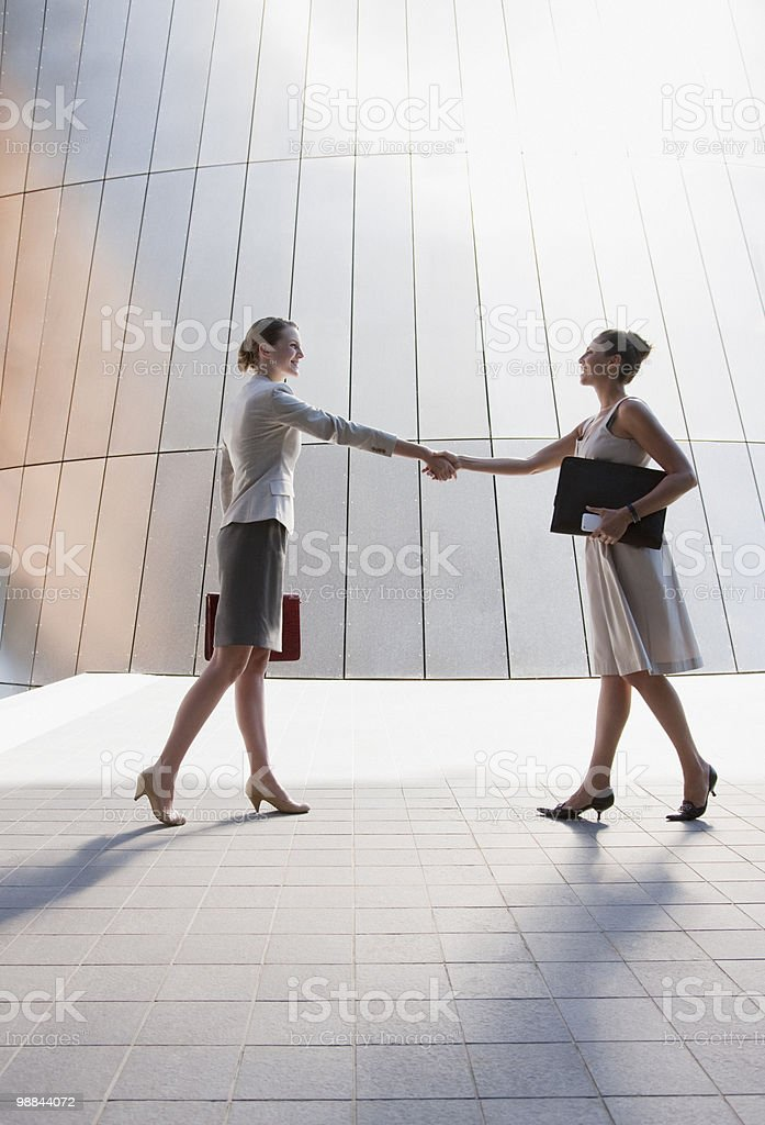 Businesswomen shaking hands outdoors stock photo