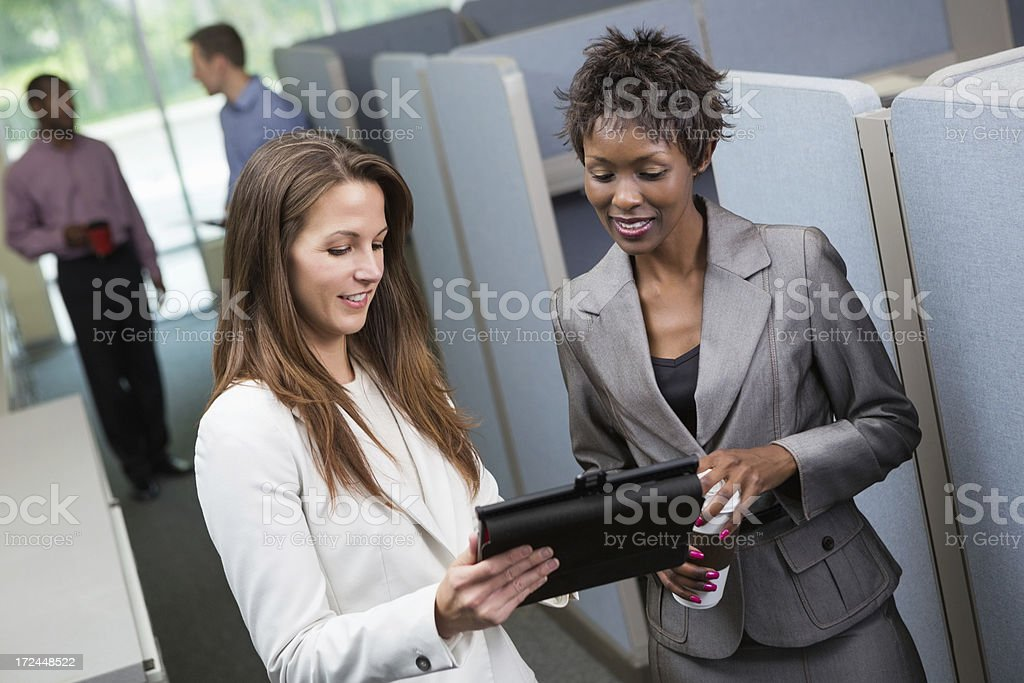 Businesswomen sharing ideas on digital tablet device outside office cubicles royalty-free stock photo