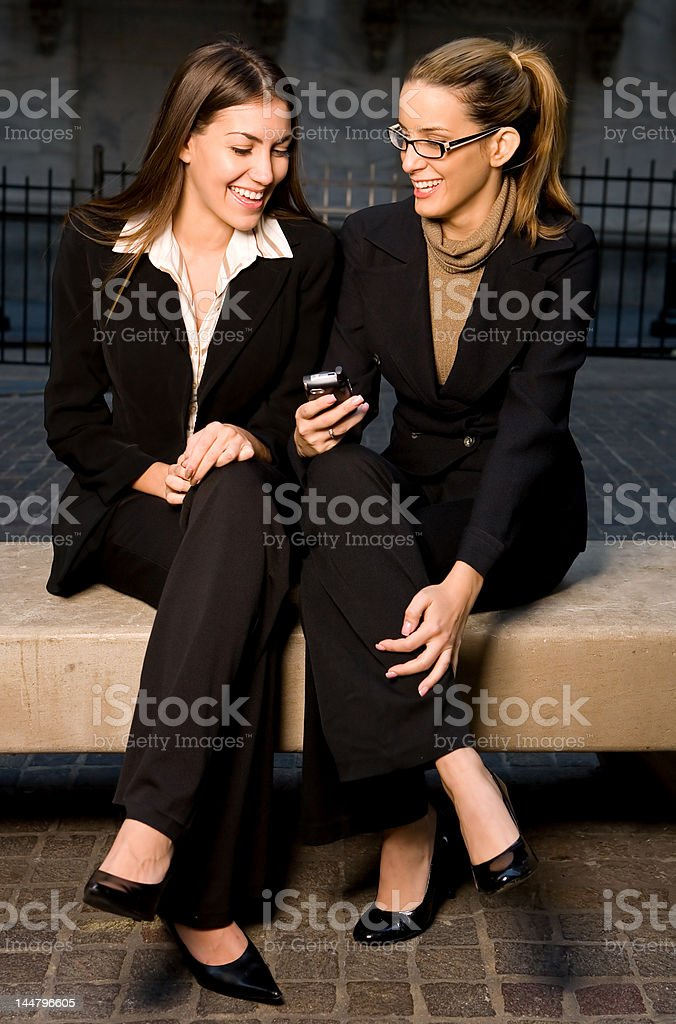 Businesswomen Sharing Info on Mobile Device royalty-free stock photo