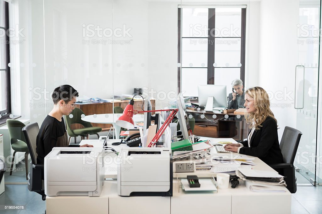 Businesswomen sitting at desk in modern office using computers stock photo