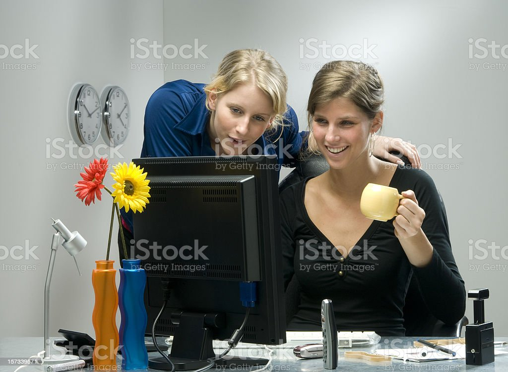 businesswomen smiling at flat screen royalty-free stock photo