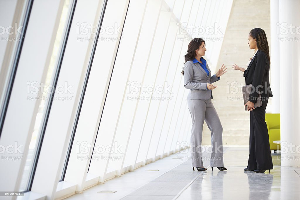 Businesswomen talking in the hall of a modern office royalty-free stock photo