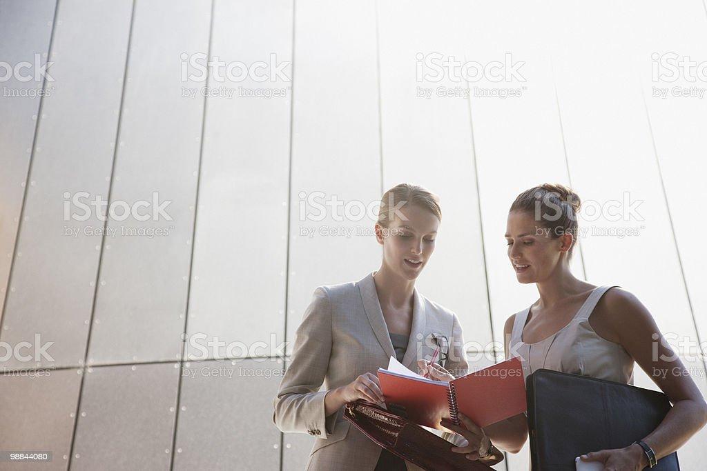 Businesswomen talking outdoors stock photo