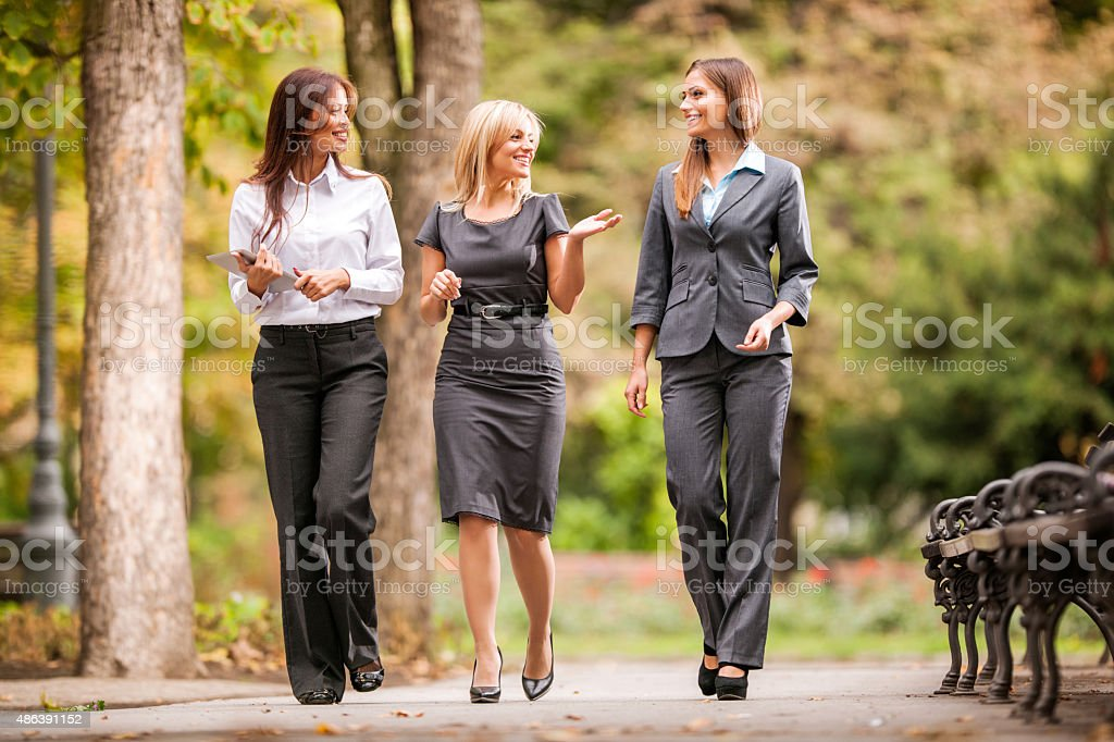 Businesswomen talking to each other while walking outdoors. stock photo