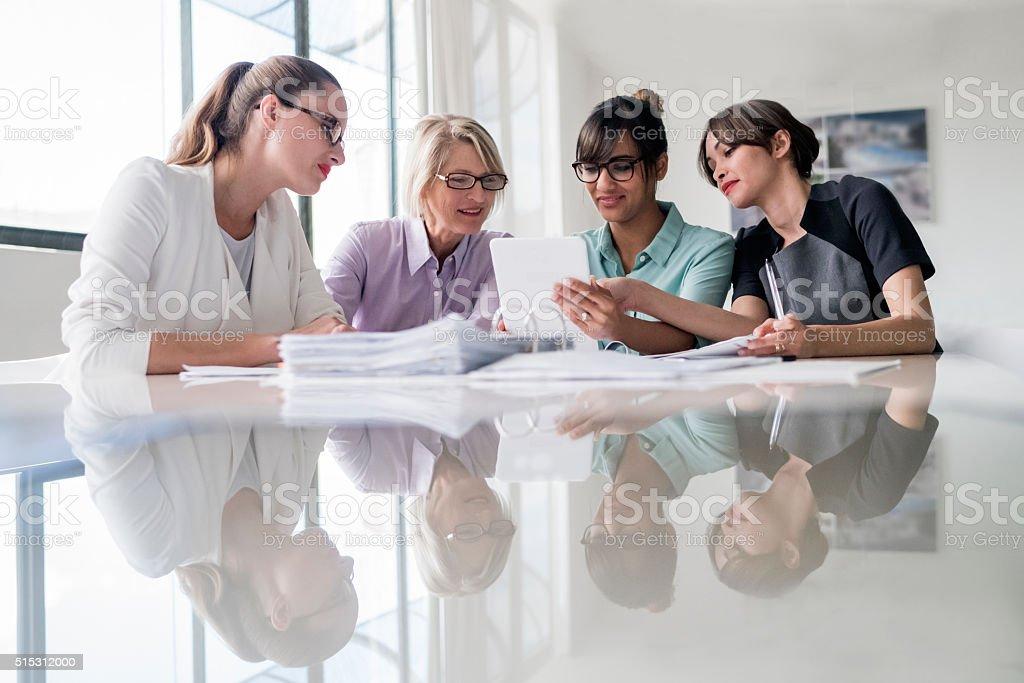 Businesswomen using digital tablet together at desk stock photo