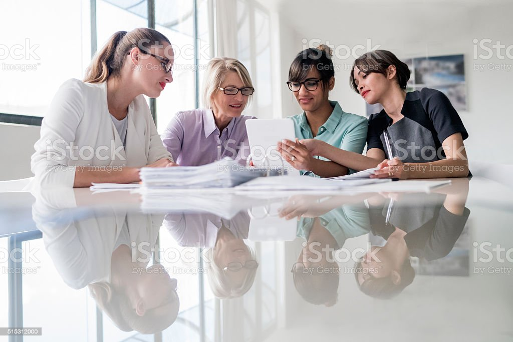 Businesswomen using digital tablet together at desk stock photo