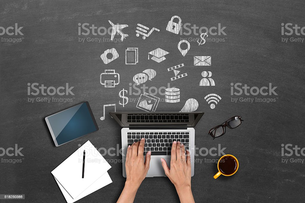 Businesswomen using laptop with variety of icons drawn on blackboard stock photo