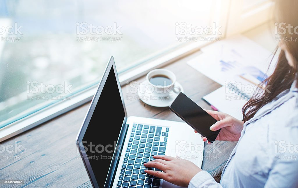 Businesswomen using mobile phone and laptop in office stock photo
