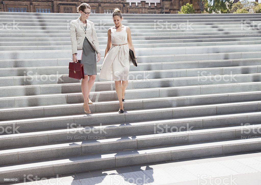 Businesswomen walking down steps outdoors royalty-free stock photo