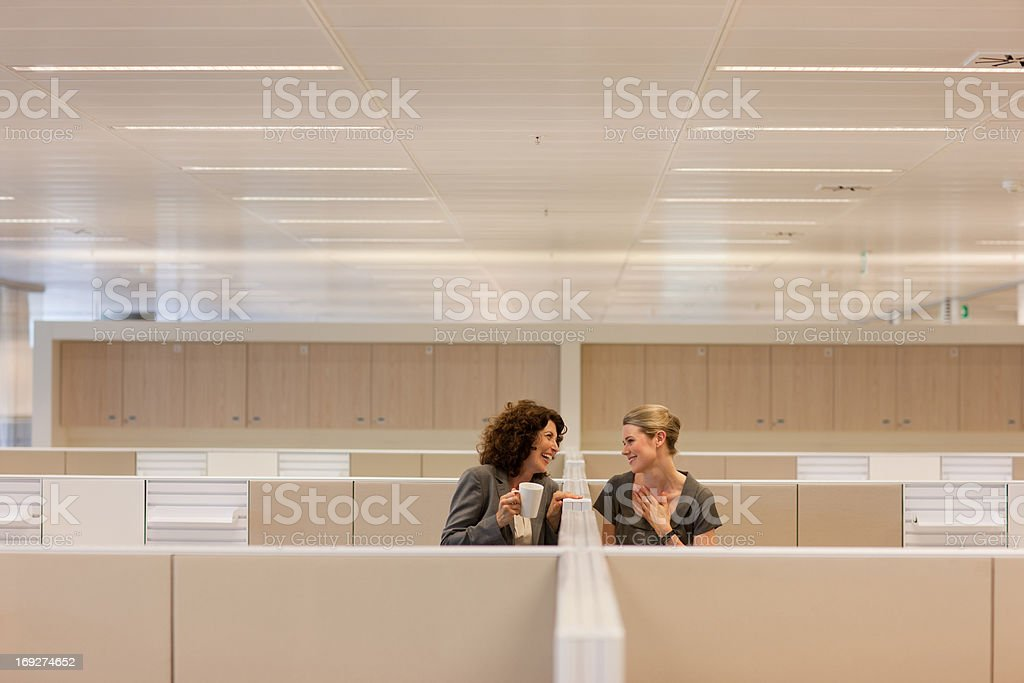 Businesswomen with coffee gossiping in office cubicles stock photo