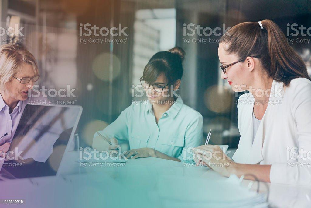 Businesswomen working at desk in office stock photo