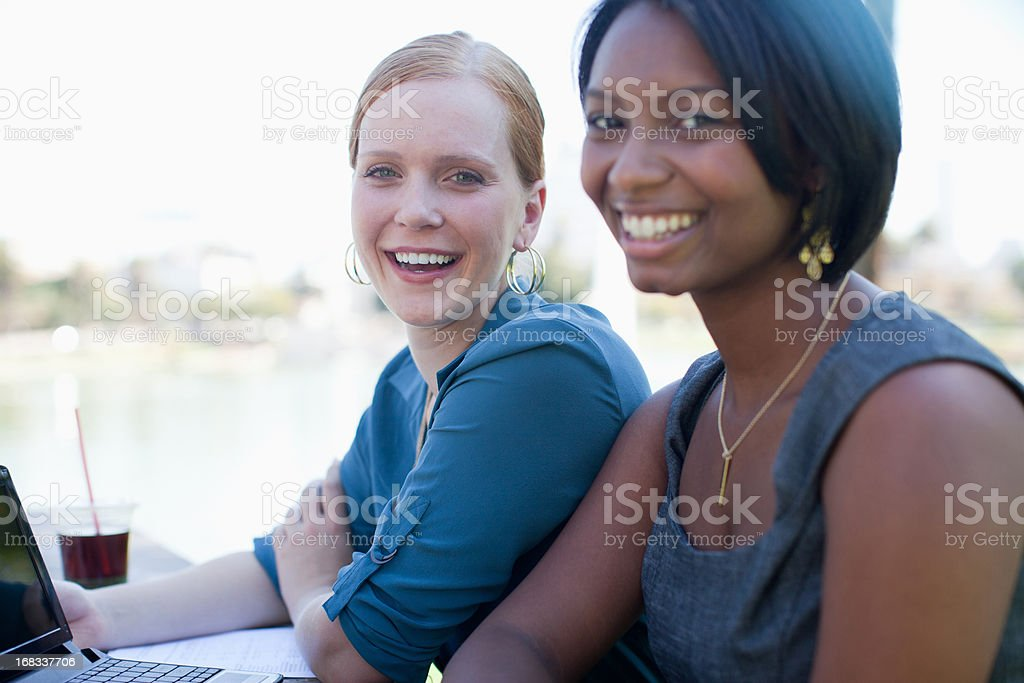 Businesswomen working on laptop in park royalty-free stock photo