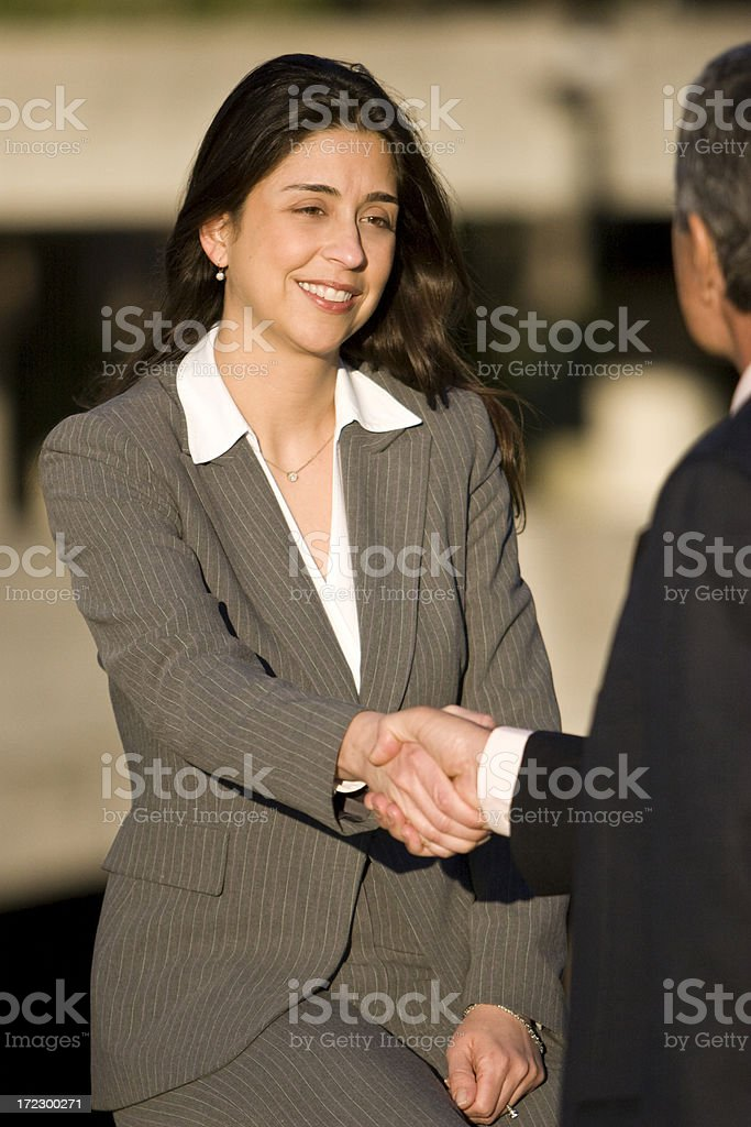 Busineswoman shaking hands with unrecognizable businessman stock photo