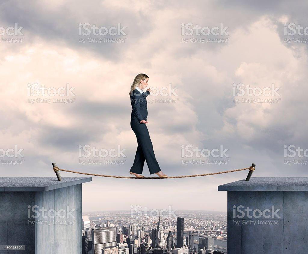 Busineswosman Balancing On A Tightrope Above Big City stock photo