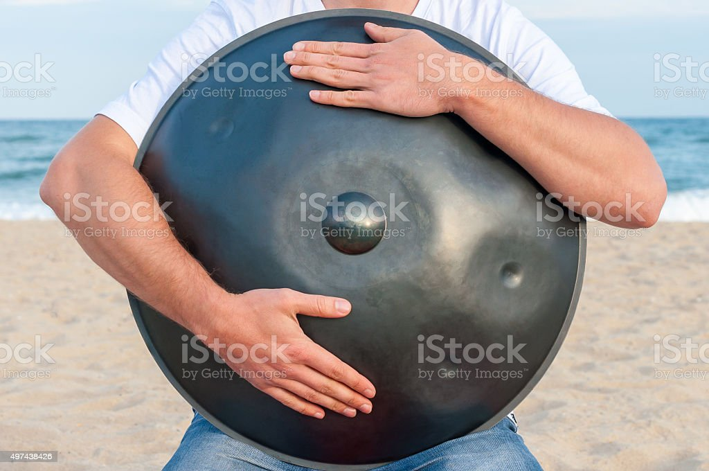 Busker hold the Hang or handpan with sea on background stock photo