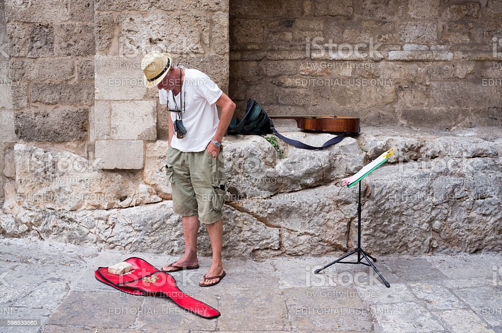 Busker looking at coins on his guitar case in Ostuni stock photo