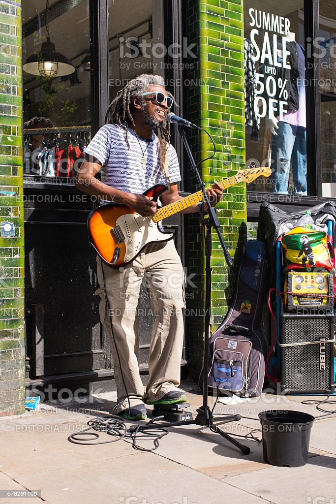 Busker musician afro artist with dreadlocks playing electric guitar stock photo